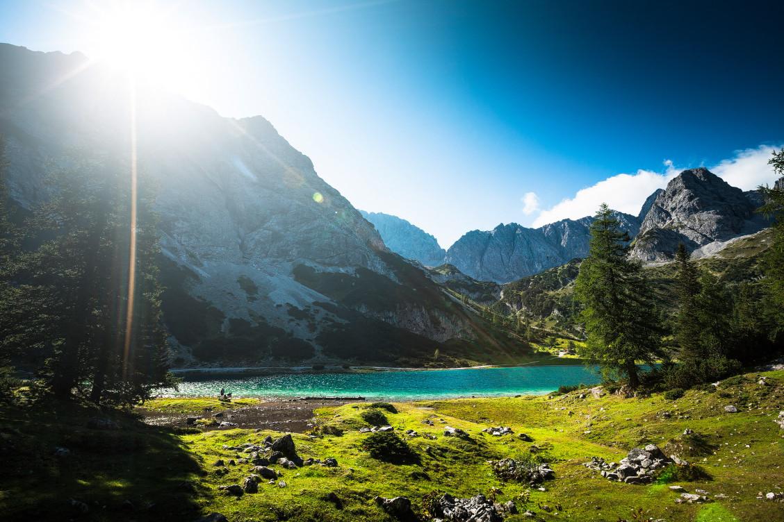 Am Ufer der Seebensees brechen die ersten Sonnenstrahlen über die Alpengipfel